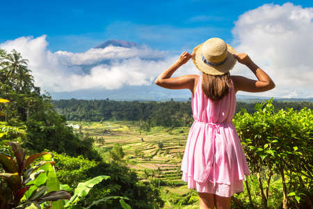 Woman traveler at  Rice terrace field and volcano Agung on Bali, Indonesia in a sunny day