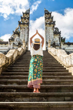 Woman traveler at Ancient gate at Pura Penataran Agung Lempuyang temple on Bali, Indonesia