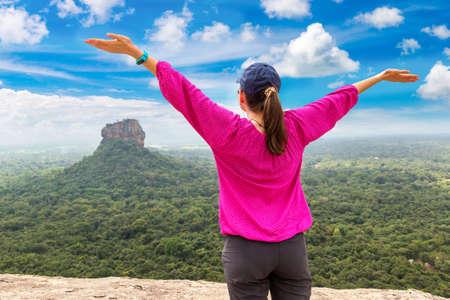 Woman rising hands on Lion Rock in Sigiriya in a sunny day, Sri Lanka Standard-Bild