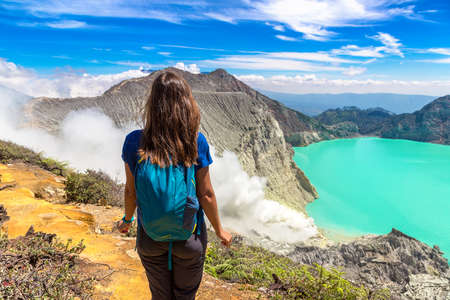 Woman traveler at crater of active volcano Ijen, Java island, Indonesia