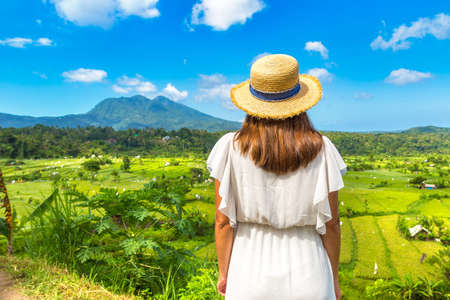 Woman traveler at Panoramic view of Rice terrace field on Bali, Indonesia in a sunny day
