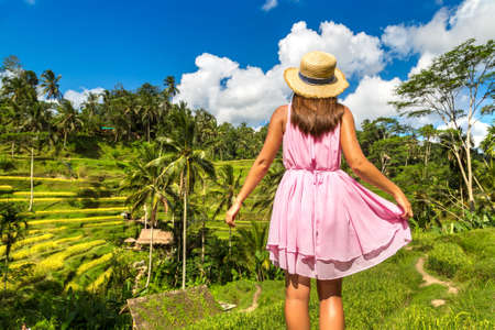Woman traveler wearing pink dress and straw hat at  Tegallalang rice terrace field on Bali, Indonesia in a sunny day Standard-Bild