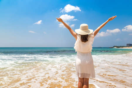 Portriat of young beautiful woman raised hands and wearing a hat and white dress staying on a tropical beach near sea