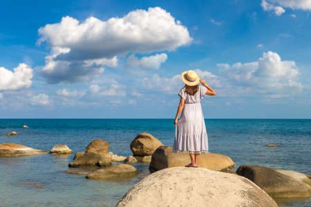 Woman traveler wearing blue dress and straw hat at  Silver Beach on Koh Samui island, Thailand in a summer day