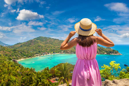 Woman traveler wearing pink dress and straw hat at viewpoint with Panoramic aerial view of Koh Tao island, Thailand