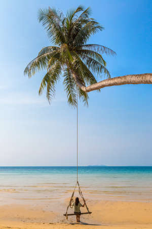 Beautiful woman swinging on palm tree over luxury tropical beach in a sunny summer day