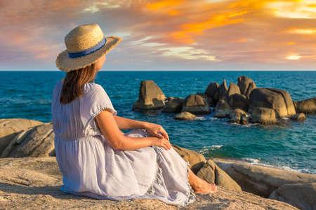 Woman traveler wearing blue dress and straw hat at  Hin Ta and Hin Yai Rocks at Samui beach, Thailand in a summy day