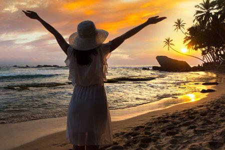 Woman looking at Sunset at Dalawella beach in Sri Lanka