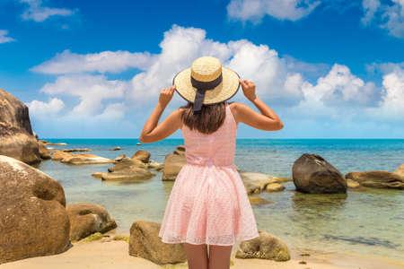 Woman traveler wearing pink dress and straw hat at  Silver Beach on Koh Samui island, Thailand in a summer day Standard-Bild