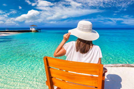 Beautiful woman relaxing in sunbed at luxury tropical beach in a sunny summer day