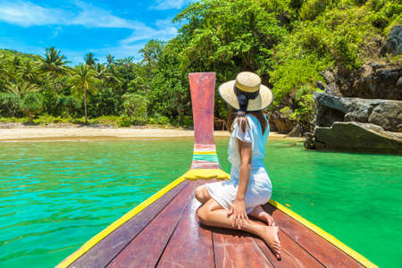 Happy traveler woman relaxing on boat near tropical island in Thailand