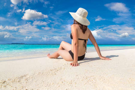 Sexy beautiful woman sitting at luxury tropical beach in a sunny summer day Standard-Bild
