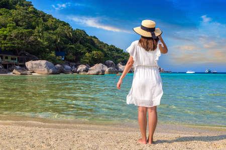 Woman traveler wearing white dress and straw hat at  Nang Yuan Island, Koh Tao, Thailand in a summer day