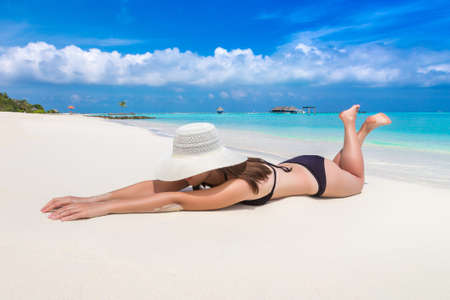 Sexy beautiful woman laying at luxury tropical beach in a sunny summer day