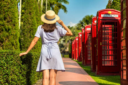 Woman traveler at Decorative English phone booths in Nong Nooch Tropical Botanical Garden, Pattaya, Thailand in a sunny day