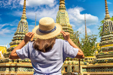 Woman traveler at  Wat Pho Temple in Bangkok in a summer day