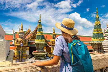 Woman traveler at Demon Guardian in Wat Phra Kaew (Temple of the Emerald Buddha), Grand Palace in Bangkok in a summer day Standard-Bild