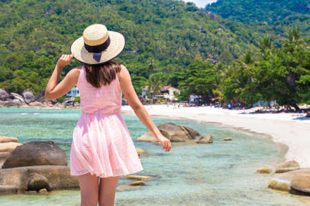 Woman traveler wearing pink dress and straw hat at  Silver Beach on Koh Samui island, Thailand in a summer day Фото со стока
