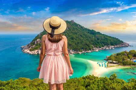 Woman traveler wearing pink dress and straw hat at Nang Yuan Island, Koh Tao, Thailand in a summer day