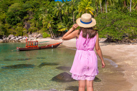 Woman traveler wearing pink dress and straw hat at  tropical beach