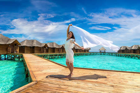 Beautiful young woman with shawl waving in wind over tropical beach jetty (wooden pier) in Maldives island