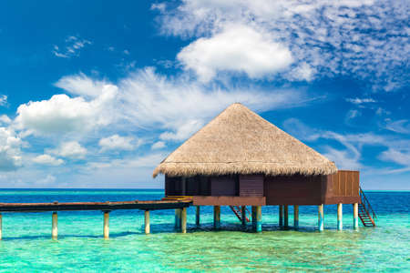Water Villas (Bungalows) and wooden bridge at Tropical beach in the Maldives at summer day Редакционное