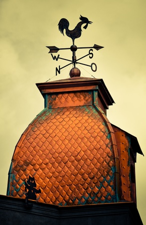A rooster weather vane silhouetted against toned sky at the top old church in Odessa photo