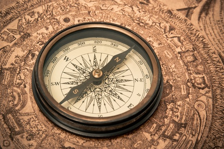 encuestando: Brújula antiguo acostado en el mapa de estilo antiguo. En tonos sepia.