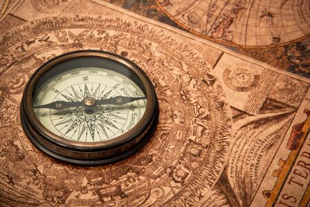 Antique compass lying on old style map. Sepia toned. Stock Photo - 9356767