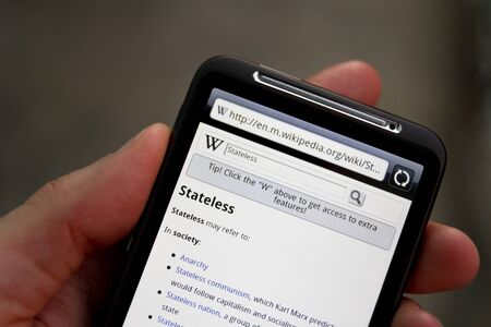 Kiev, Ukraine - May 20, 2011: Hand hold HTC Desire HD with Wikipedia search web page on screen.