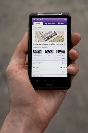 Kiev, Ukraine - May 20, 2011: Hand holding HTC Desire HD showing Yahoo news on screen.