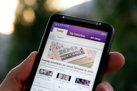 Kiev, Ukraine - May 20, 2011: Hand holding HTC Desire HD showing Yahoo news on screen. Stock Photo - 9726075