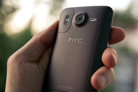 Kiev, Ukraine - May 20, 2011: Hand hold a brown HTC Desire HD smartphone. Backside view.