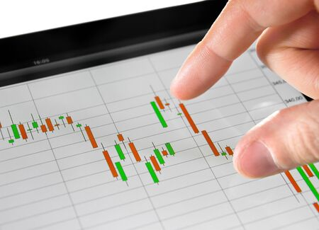 Touching stock market graph on a touch screen device. Stock Photo - 9830733