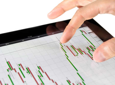 stock trading: Using touch screen tablet for analyzing stock market chart. Stock Photo