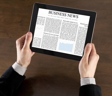 Businessman hands are holding the touch screen device with business news on screen photo
