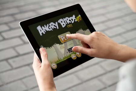 Kiev, Ukraine - July 31, 2011 - A woman outdoors play in the game Angry Birds on Apple Ipad2. This second generation Ipad2 is designed and development by Apple inc. and launched in march 2011. Angry Birds is most popular game, developed by Rovio Mobile st