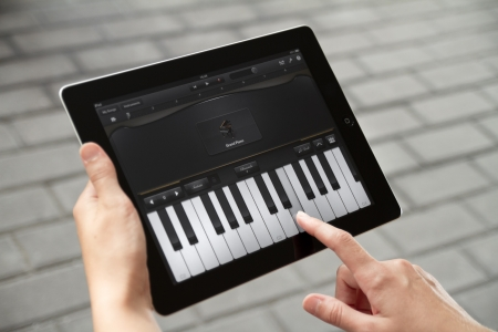 Kiev, Ukraine - July 31, 2011 - A woman outdoors playing the piano, which included in GarageBand application on Apple Ipad2. This second generation Ipad2 is designed and development by Apple inc. and launched in march 2011. GarageBand very popular enterta Editorial