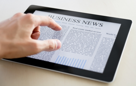 Man hands are pointing on touch screen device with business news. Stock Photo - 10365287