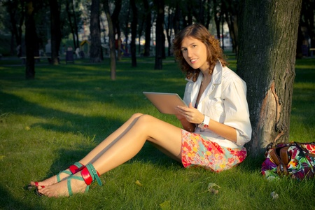 A young woman uses tablet pc device in a park sitting near a tree.