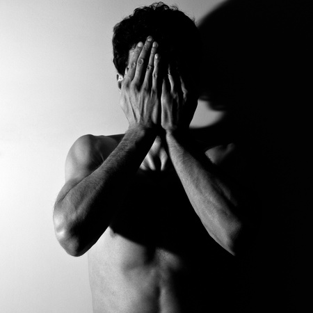 Portrait of a young man covering his face in hands. Stock Photo - 11049090