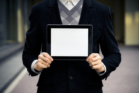 Businessman shows digital tablet pc with blank screen.