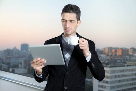 Businessman with a cup of coffee uses a digital tablet on the roof of business center. Stock Photo - 11132970