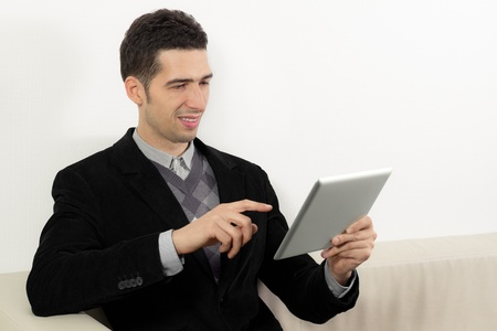 Businessman sitting on sofa and using a digital tablet pc. photo
