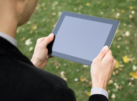 Businessman in a park holding a touch screen device. photo