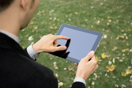 Businessman outdoors working with touch screen device. photo