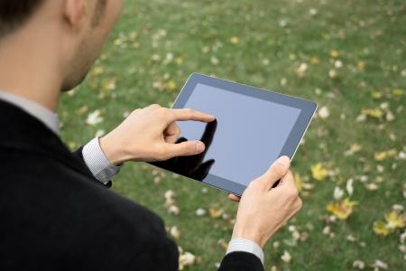 �cran tactile: Homme d'affaires travaillant avec l'ext�rieur appareil � �cran tactile. Banque d'images