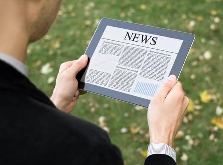 lezing: Zakenman het lezen van nieuws over digitale tablet op park. Stockfoto