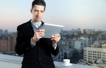 Businessman with a cup of coffee uses a digital tablet on the roof of business center.