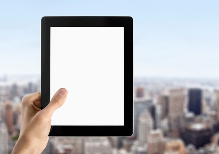 Man hands are holding touch screen device with blank screen. Blurred cityscape with skyscrapers on background. Stock Photo - 11387994
